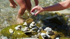 Het kind en zijn moeder zetten kiezelstenen op het strand met hun eigen handen, close-up, in langzame motie stock footage