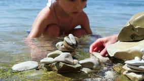 Het kind en zijn moeder zetten kiezelstenen op het strand met hun eigen handen, in langzame motie, close-up stock videobeelden