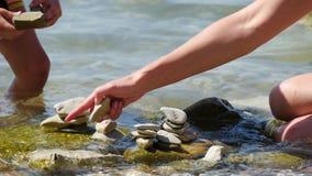 Het kind en zijn moeder zetten kiezelstenen op het strand met hun handen, close-up stock video