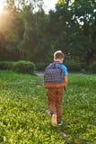 Het kind gaat naar school de jongensschooljongen gaat naar school in de ochtend gelukkig kind met een binnen aktentas op zijn rug stock fotografie