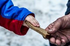 Het kind geeft de man een stuk van roggebrood stock afbeelding