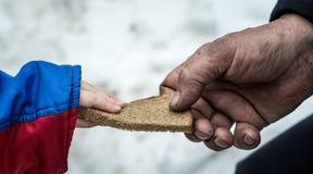 Het kind geeft de man een stuk van roggebrood royalty-vrije stock afbeeldingen