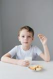 Het kind is gelukkig om eigengemaakte koekjes met melk te eten royalty-vrije stock afbeelding