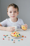 Het kind is gelukkig om eigengemaakte koekjes met melk te eten stock foto's
