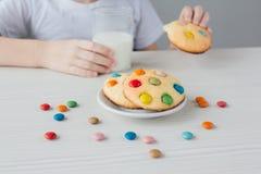 Het kind is gelukkig om eigengemaakte koekjes met melk te eten royalty-vrije stock foto's