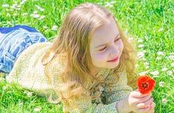 Het kind geniet van geur van tulp terwijl het liggen bij weide Allergieconcept Meisje met lang haar die op grassplot, gras liggen stock foto's