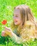 Het kind geniet van geur van tulp terwijl het liggen bij weide Meisje met lang haar die op grassplot, grasachtergrond liggen De l royalty-vrije stock foto