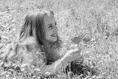 Het kind geniet van geur van tulp terwijl het liggen bij weide Meisje met lang haar die op grassplot, grasachtergrond liggen Parf royalty-vrije stock fotografie