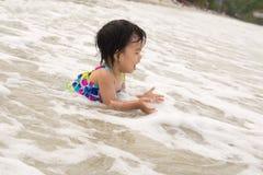 Het kind geniet van golven op strand Royalty-vrije Stock Afbeeldingen