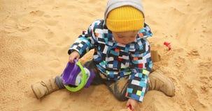 Het kind graaft koud het zand stock video