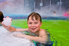 Het kind heeft pret in de openlucht thermische pool stock fotografie