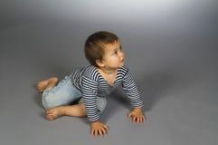 Het kind in het gestreepte vest van de zeeman kruipt Stock Foto