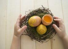 Het kind houdt het bruine ei met een patroon Geschilderde bruine eieren Stock Fotografie