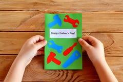 Het kind houdt de groetkaart van de vadersdag in zijn handen Royalty-vrije Stock Foto