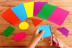 Het kind houdt de schaar in zijn handen en snijdt een vierkant van kleurenkarton Vroeg kinderjarenonderwijs stock afbeelding