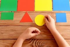 Het kind houdt een gele kartoncirkel in zijn handen en zet op een overeenkomstige kleurenkaart Het kind leert kleuren Stock Foto