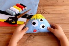 Het kind houdt een gevoeld monster in zijn handen Gevoeld Halloween-ornament Royalty-vrije Stock Afbeeldingen