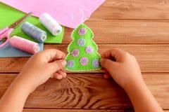 Het kind houdt een gevoelde Kerstboom in zijn handen Groene gevoelde die bontboom met roze en blauwe ballen wordt verfraaid Stock Foto