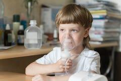 Het kind houdt een inhaleertoestel van de maskerdamp royalty-vrije stock foto