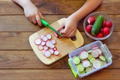 Het kind houdt een keukenmes in hand en snijdt radijs Stock Foto's