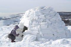 Het kind houdt een sneeuwbal hurkend bij de ingang aan het huis van Eskimo's - iglo stock fotografie