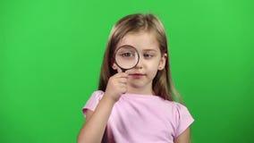 Het kind houdt een vergrootglas Het groene scherm Langzame Motie stock video