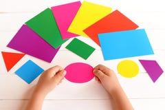 Het kind houdt karton roze ovaal in de handen Het kind leert kleuren en geometrische vormen Het ontwikkelen van vaardigheden in j royalty-vrije stock afbeelding