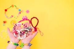Het kind houdt kinderen` s juwelen Stock Afbeeldingen