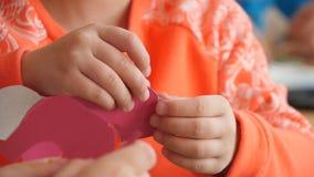Het kind houdt schaar in haar handen en besnoeiingen Materialen voor ambachten op de lijst Met de hand gemaakt Handwerk voor kind stock videobeelden