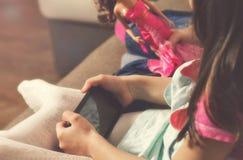 Het kind houdt smartphone terwijl thuis het zitten op laag stock afbeeldingen