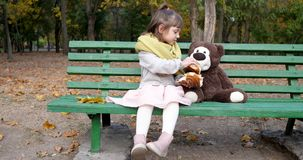 Het kind houdt twee stukken in openlucht van broodje met papaverzitting dichtbij teddybeer op bank bij speelplaats in park stock videobeelden