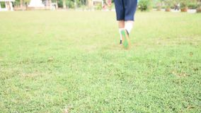 Het kind houdt voetbal op groen gras Sluit omhoog stock footage