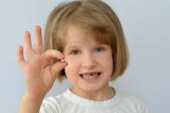 Het kind, jong geitje, toont de gevallen melktand Stock Foto