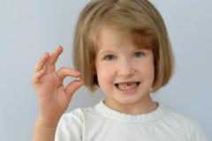 Het kind, jong geitje, toont de gevallen melktand Stock Foto's