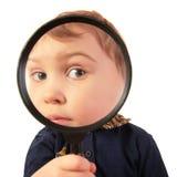 Het kind kijkt door meer magnifier Stock Foto's
