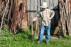 Het kind kleedde zich als landbouwer met hooivork Stock Foto