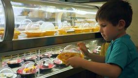 Het kind in koffie neemt een gebraden kip van de bewegende transportbandlijn met verschillend voedsel in kantine en gaat zitten b stock video