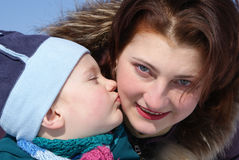 Het kind kust zijn moeder Stock Foto's
