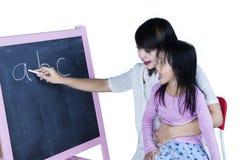 Het kind leert alfabet met haar mamma Stock Foto's