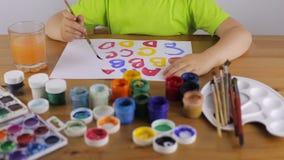 Het kind leert om brieven met verf te schrijven stock videobeelden