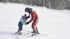Het kind leert om met een instructeur te skien Het van brandstof voorzien van de benzinepomp Actieve sport stock footage