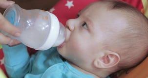 Het kind leert om van een fles te drinken stock footage