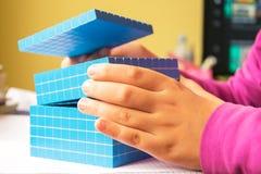 Het kind leert wiskunde, volume en capaciteit Voor het leren van modelgebruik een driedimensionele kubus stock foto