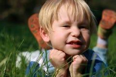 Het kind legt op een groen gras Stock Foto's