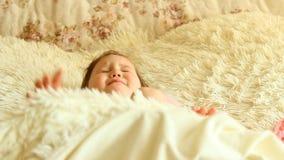 Het kind ligt aan slaap op het bed en sluit zijn ogen stock videobeelden