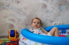 Het kind ligt in een kinderen` s pool met speelgoed royalty-vrije stock afbeeldingen