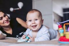 Het kind ligt op een bed met moeder in een milieu van kinderen` s speelgoed Stock Foto's