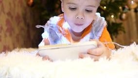 Het kind ligt op een zachte witte deken in de ruimte van de kinderen Hij let op beeldverhalen op smartphone Kerstmis stock videobeelden
