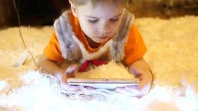 Het kind ligt op een zachte witte deken in de ruimte van de kinderen Hij let op beeldverhalen op smartphone Kerstmis stock footage