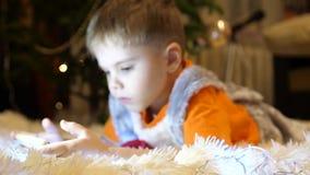Het kind ligt op een zachte witte deken in de ruimte van de kinderen Hij let op beeldverhalen op smartphone Kerstmis stock video